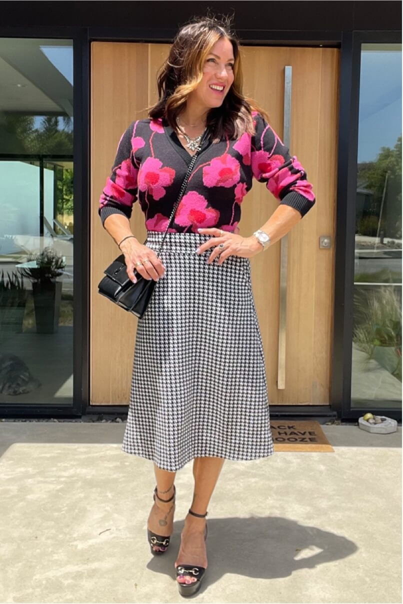 Kat Woodside, Chief Design Officer models her outfit of the day featuring the Rococo Pullover in Poppy Bloom and statement accessories