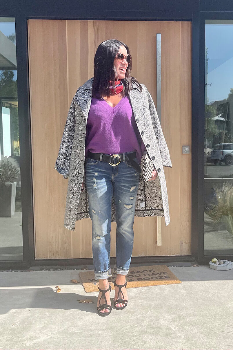 Kat Woodside, Chief Design Officer models her outfit of the day featuring the Luxury Pullover in Violet, 100% Boyfriend in Craftsman Wash, King Cobra Coat in Snake and the Coy Scarf in Multi.